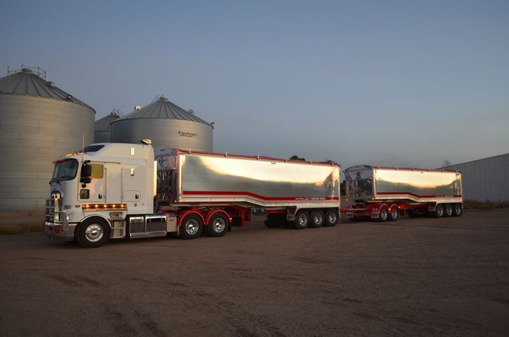 PBS A-double grain trailers for Narrain Grains. In front of grain silo and shed.